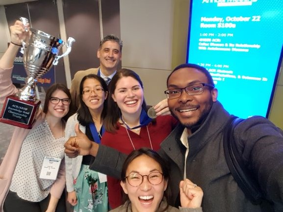 Group photo of ACGME Fellows posing with Knowledge Bowl trophy